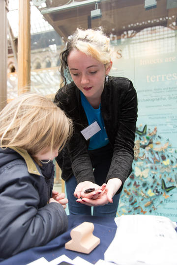Museum staff with children looking at specimens on a table in the Museum